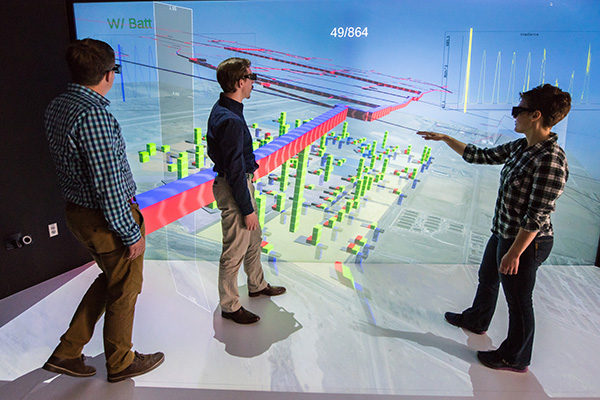 NREL engineers stand in front of a 3D model of a district showing energy flow.
